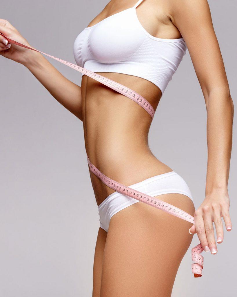 Mujer con cuerpo delgado y midiéndose con una cinta métrica, la reducción de medidas es un must en corporales