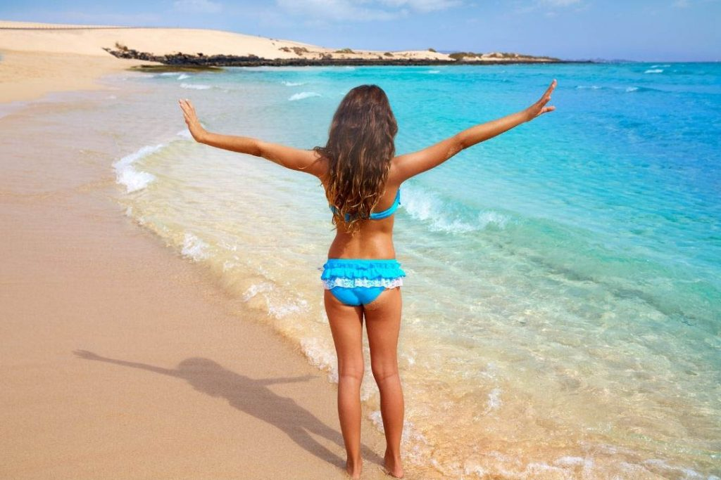 Mujer en la playa con bikini azul alzando sus manos
