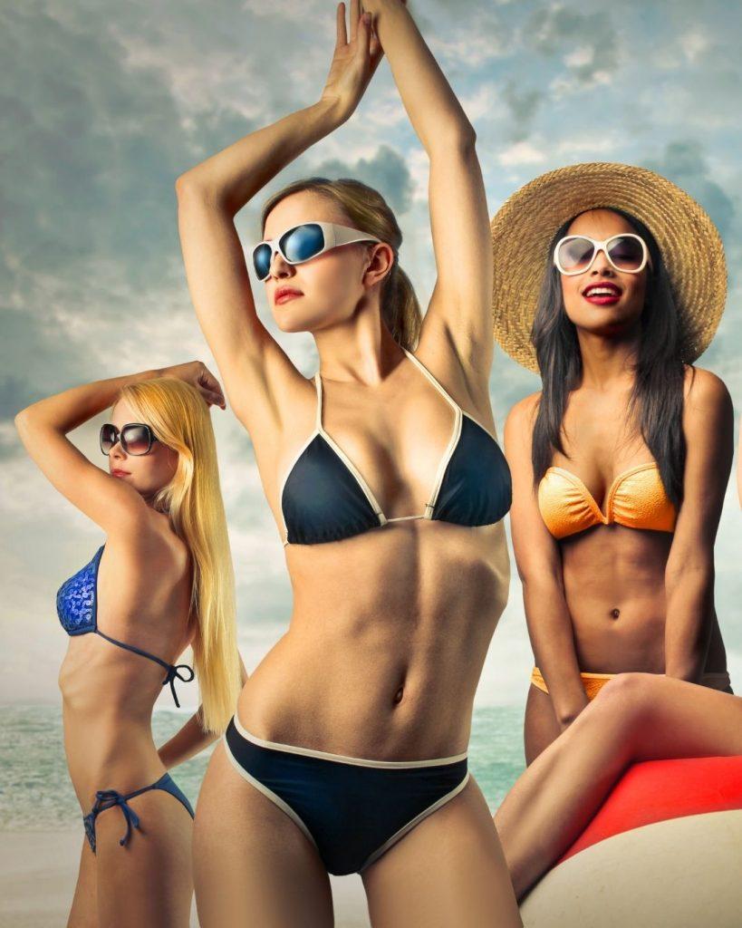 Grupo de mujeres con depilación definitiva en la playa con bikini