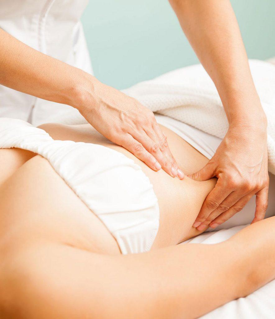 Mujer recostada recibiendo un masaje de drenaje linfático
