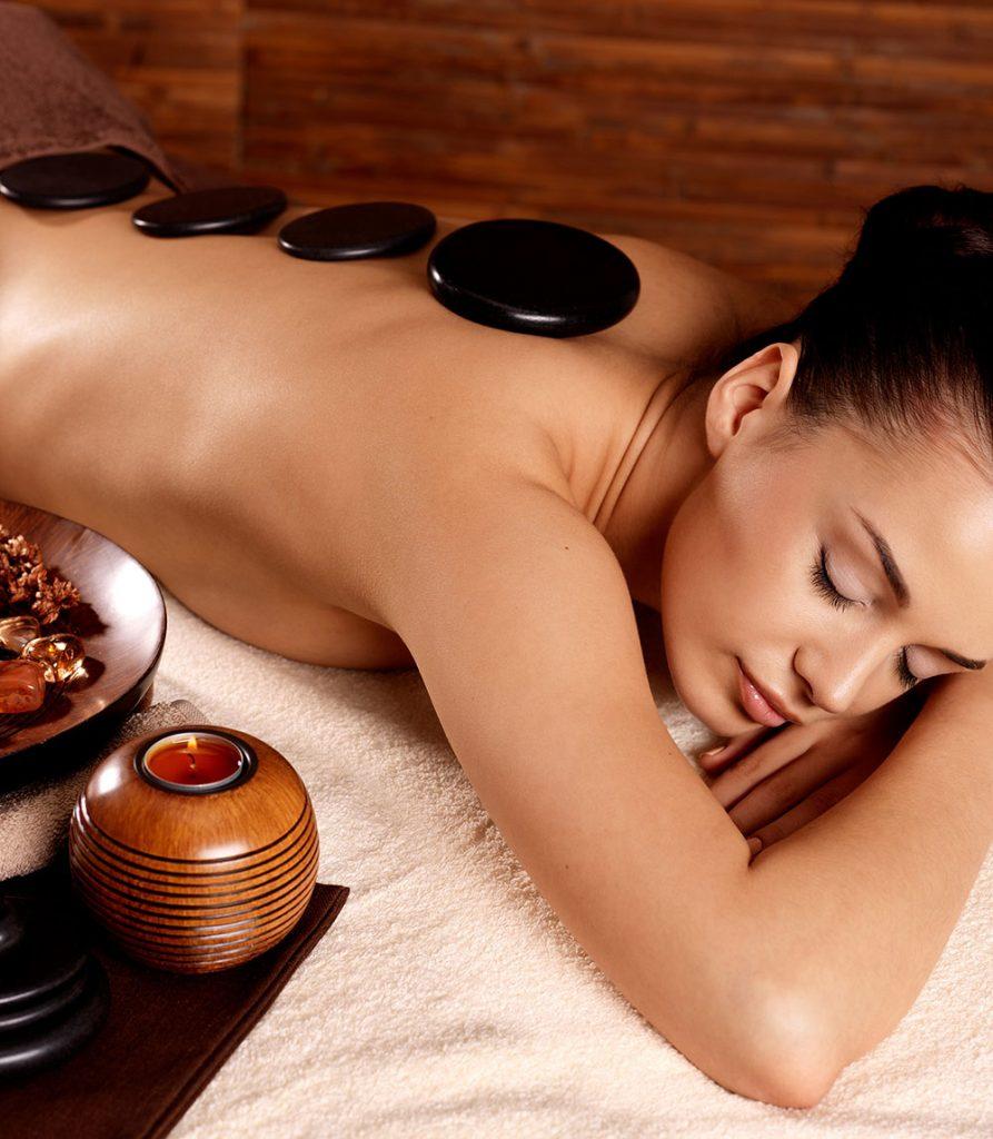 Mujer recostada en camilla tomando un masaje de piedras calientes