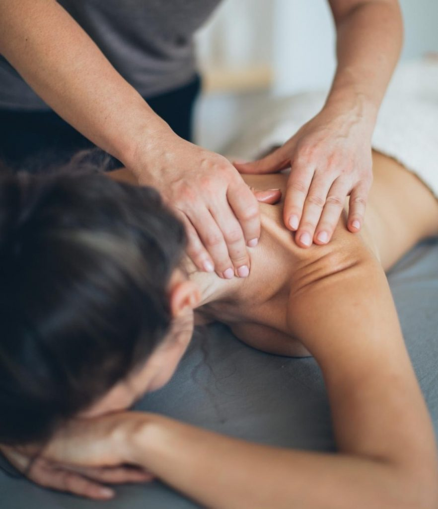 Mujer posición boca abajo, recibiendo un masaje en las espalda alta