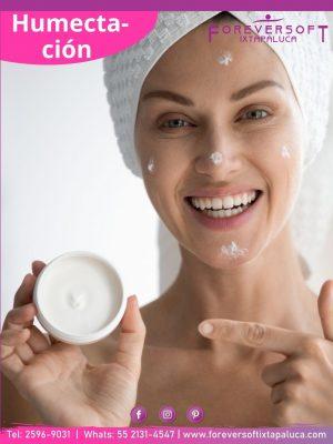 Mujer recien salida de bañarse aplicando una crema humectante